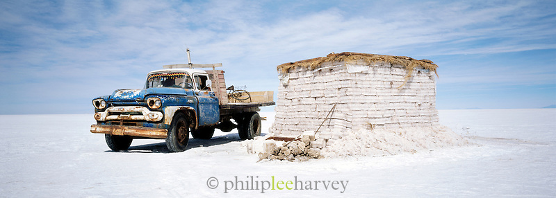A pick up truck next to stacked up salt bricks on Salar de Uyuni salt flats, Potosi, Bolivia. The Salar de Uyuni are the worlds largest salt flats.