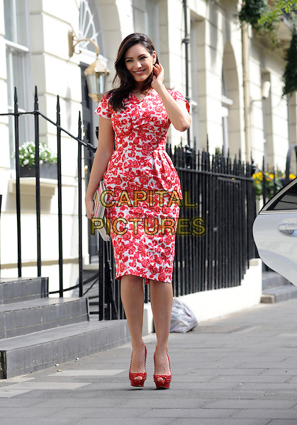 Kelly Brook.Spotted in London, England..April 24th, 2013.full length red white floral print dress peep toe platform shoes clutch bag pink peplum hand arm   .CAP/AOU.©AOU/Capital Pictures.
