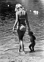 Mom wades with her child to cool off in  Lake Temescal.on a hot July day in Oakland, California. (1973 photo by Ron Riesterer)