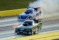Sept. 21, 2012; Ennis, TX, USA: NHRA funny car driver Alexis DeJoria (near lane) races alongside a tire smoking Robert Hight during qualifying for the Fall Nationals at the Texas Motorplex. Mandatory Credit: Mark J. Rebilas-