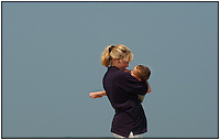 A mother hugs her son (she is lifting him up). Clean background, clear sky behind them.  Photo is model released.