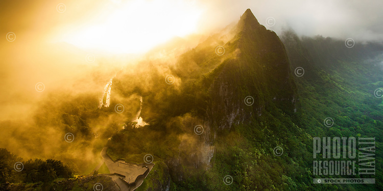 Mist rolls over the Pali lookout and Ko'olau Range at sunset on O'ahu.