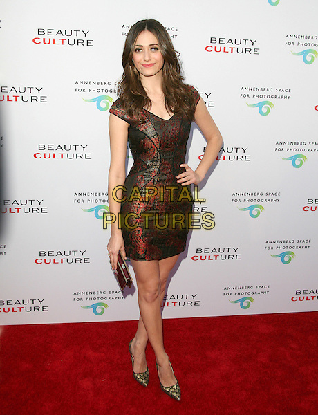 EMMY ROSSUM.at The opening of BEAUTY CULTURE, a photographic exploration of how feminine beauty is defined, challenged and revered in modern society held at Annenberg Space for Photography in Century City, California, USA,.May 19th 2011..full length red shiny print dress clutch bag brown pointy shoes gold  hand on hip                                                                    .CAP/RKE/DVS.©DVS/RockinExposures/Capital Pictures.