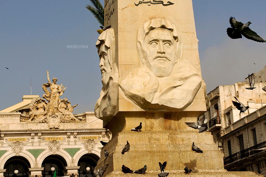 Algerie. Ville d'Oran. Place d'armes ou place du 1er Novembre. 8 Avril 2011 ..Sur la place du Premier Novembre, au c?ur d'Oran, un obelisque a ete erige a la gloire des soldats francais morts sous les coups des cavaliers de l'Emir Abd el-Khader (1808-1883) pendant la bataille de Sidi-Brahim. Apres l'Independance, les Algeriens ajoutent sur les quatre cotes du monument, le portrait sculpte du heros. En hommage au soufi qu'il incarnait et a sa victoire contre les troupes francaises, un verset est inscrit au-dessus de son buste : « La victoire et la croyance appartiennent a Dieu. Certes Allah est tout-puissant et sage.» ..Algeria, city of Oran. The Place d'Armes, also calledPlace du 1er novembre. April 8, 2011..On the Place d'Armes, in the heart of Oran, an obelisk was erected in memory of the French soldiers killed by the troops of Emir Abd al-Q?dir (1808-1883) during the battle of Sidi-Brahim. After the War of Independence, the Algerian people had the bust of Abd al-Q?dir added at the bottom of each side of the obelisk. In honor of this hero and Sufi, and to commemorate his victory against the French troops, a verse was written above his bust: ?Victory cometh only by the help of Allah. Lo! Allah is mighty and wise.?..
