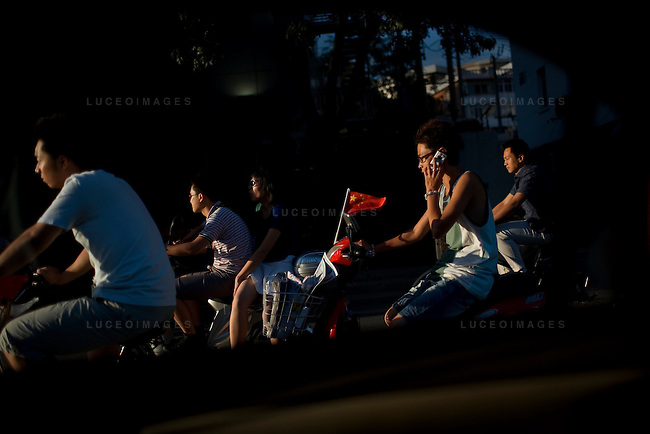 Locals ride towards the Tainjin Olympic Center Stadium for a football match in Tainjin, China on Friday, August 15, 2008.  Kevin German