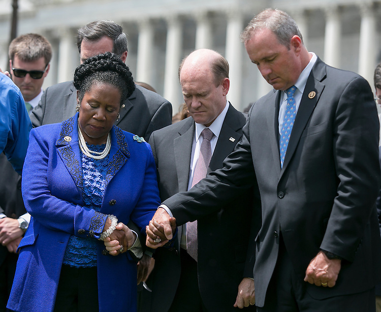 UNITED STATES - JUNE 18 - From left, Rep. Sheila Jackson Lee, D-Texas, Sen. Chris Coons, D-Del., and Rep. Jeff Duncan, R-S.C., hold hands during a prayer vigil for victims of the Charleston shooting, outside of the U.S. Capitol on Thursday, June 18, 2015. (Photo By Al Drago/CQ Roll Call)