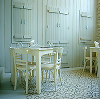 Small white painted tables grouped on a mosaic floor have been set for lunch