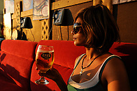 TURKEY Istanbul, woman drinks turkish Efes beer in Pub under bridge over Golden Horn/ TUERKEI Istanbul, Frau trinkt Efes Bier