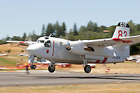 A Calfire Grumman S2-T Turbo Tracker based in Columbia, California, gets airborne in response to a forest fire. The Turbo Tracker is a civilian conversion of the Navy's S-2 Tracker. The Calfire fleet, formerly California Department of Forestry, includes 23 of the Turbo Trackers located throughout the state. Each aircraft is capable of carrying 1200 gallons of water or retardant and able to reach a fire within 20 minutes. Photographed 06/07