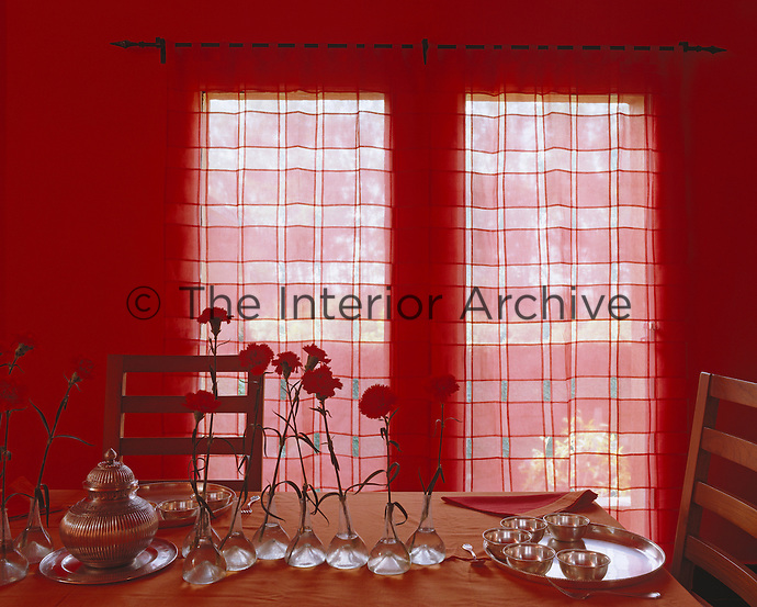 Sheer curtains diffuse the light coming into this red dining room