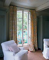 A pair of armchairs and a pair of wardrobes either side of French windows leading out to the balcony