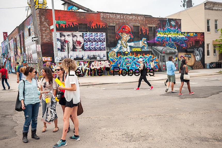 """Thousands pour into Bushwick, Brooklyn in New York for the annual Bushwick Collective Block Party on Saturday, June 4, 2016. Music and partying brought some but the real attraction was the new murals  by """"graffiti"""" artists that decorate the walls of the buildings that the collective uses.  (©Richard B. Levine)"""
