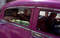 folks laughing in pink oldtimer, american car in Havana, Cuba