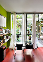 A modern home study with vibrant green walls and a red floor. A glass table stands next to two book shelves. A full height glass door leads to a garden beyond.