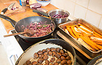 Vegan meal cooking on stove with chestnuts, onions, carrots, parsnips, cabbage