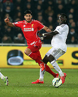 SWANSEA, WALES - MARCH 16: Emre Can of Liverpool (L) gets the ball past Bafetimbi Gomis of Swansea (R) during the Premier League match between Swansea City and Liverpool at the Liberty Stadium on March 16, 2015 in Swansea, Wales