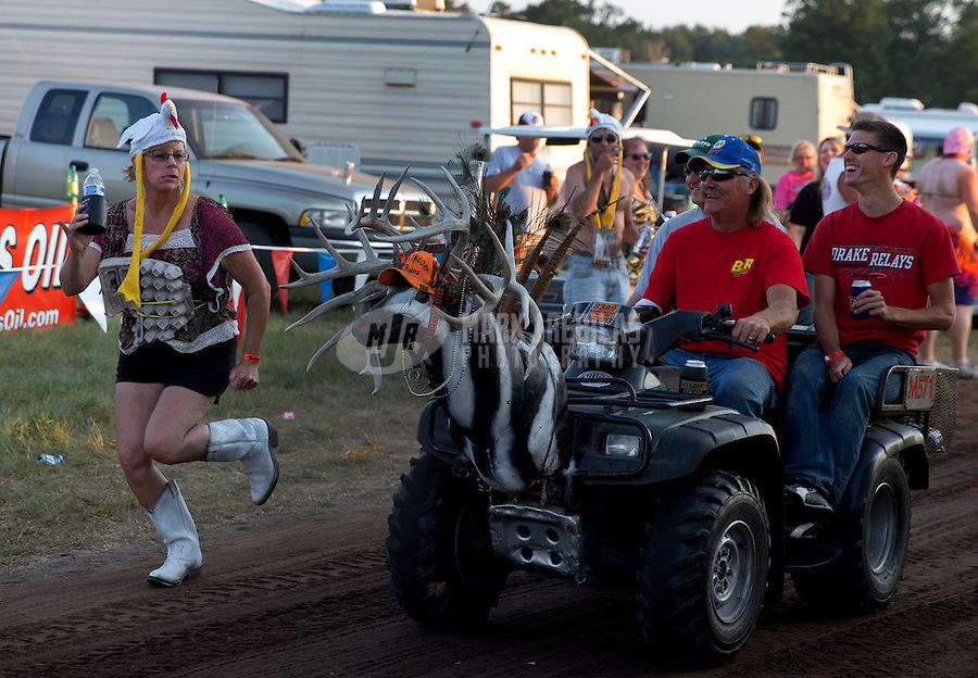 Aug. 17, 2013; Brainerd, MN, USA: A female NHRA fan chases a quad in the Zoo campground outside of the pit area following qualifying for the Lucas Oil Nationals at Brainerd International Raceway. Mandatory Credit: Mark J. Rebilas-