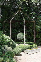 An iron gazebo from Anthropologie sits at the end of the gravel driveway