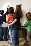 public school elementary school Grade 6 group writing on white board during presetation to class vertical differing heights and stages of development