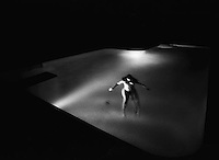 Female figure floating in swimming pool at night<br />
