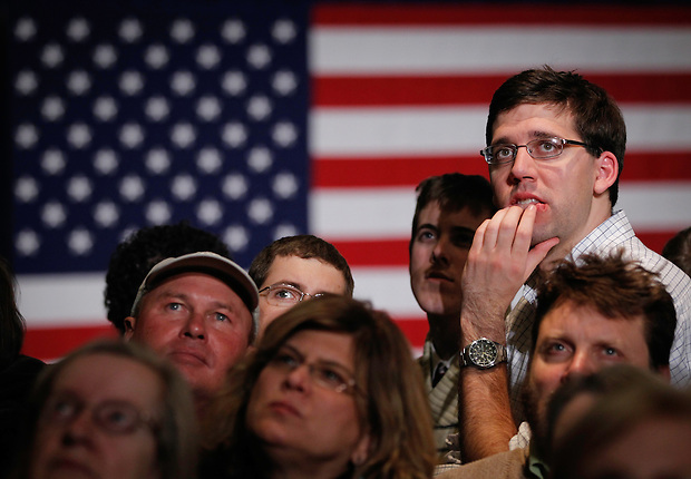 WILLIAM OSBERGHAUS, right, of St. Louis, Mo. watches the close Iowa caucus results with others at Mitt Romney's rally site following the Iowa caucus Tuesday, January 3, 2012 in Des Moines, Iowa.