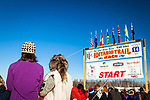 Visitor watching Iditarod 2014 Restart by the Start sign, Willow, Southcentral Alaska, Winter.
