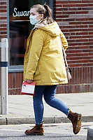 Pictured: A woman wears a face mask as she walks by Castle Street in Swansea, Wales, UK. Saturday 21 March 2020<br /> Re: Covid-19 Coronavirus pandemic, UK.