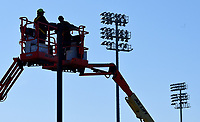 NWA Democrat-Gazette/DAVID GOTTSCHALK The stadium lights from Arrest Ballpark are visible Friday, March 22, 2019, behind Jesse Stamps (left), and Adam Hunt, service technicians with Multi-Craft Contractors , Inc. of Springdale, as they work on the parking lot lights at the ballpark in Springdale. The technicians  were converting the lights to light-emitting diodes.