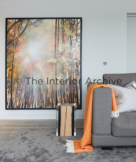 The orange tones in the painting on the wall are picked up in the woollen throw draped over the arm of the grey sofa.