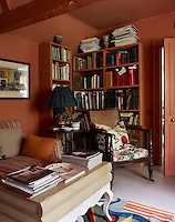 The walls and bookshelves in the cosy library have been painted to match in a warm and vibrant terracotta