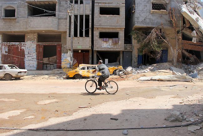 A Palestinian rides a bicycle past the remains of house, which witnesses said was hit by an Israeli air strike, in Nuseirat refugee camp in the central Gaza Strip on August 9, 2014. Israel launched more than 20 aerial attacks in Gaza early on Saturday and militants fired several rockets at Israel in a second day of violence since a failure to extend an Egyptian-mediated truce that halted a month long war earlier this week. The Israeli military said that since midnight it had attacked more than 20 sites in the coastal enclave where Hamas Islamists are dominant, without specifying the targets. Medical officials in Gaza said two Palestinians were killed when their motorcycle was bombed and the bodies of three others were found beneath the rubble of one of three bombed mosques. The air strikes which lasted through the night also bombed three houses, and fighter planes also strafed open areas, medical officials said. Photo by Khaled al-Sabbah