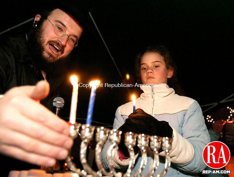 WATERBURY, CT 26 December 2005 -122605BZ02-   <br /> Rabbi Joseph Eisenbach holds his hand up to block the wind after Sima Weissman, 12, of Bloomfield, lit the candles during a menorah lighting on the green in Waterbury Monday night.  The lighting is sponsored by the Chabad Lubavitch of the Northwest Corner.   <br /> Jamison C. Bazinet Republican-American