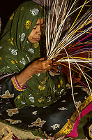 Qurum, Oman.  Middle-aged Woman Working with Straw to Make a Basket.  Muscat Festival, demonstrating traditional crafts.