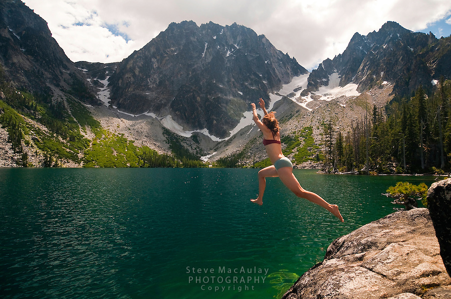 Young woman leaping into the emerald green water of Colchuck Lake, Alpine Lakes Wilderness, WA.