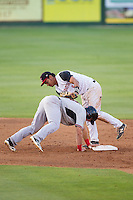 Nick Vickerson (21) of the Hickory Crawdads gets back to second base ahead of the tag of Kannapolis Intimidators shortstop Cleuluis Rondon (5) at CMC-Northeast Stadium on May 18, 2014 in Kannapolis, North Carolina.  The Intimidators defeated the Crawdads 6-5 in 10 innings.  (Brian Westerholt/Four Seam Images)