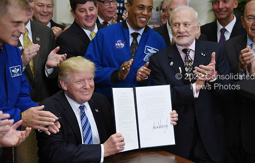 United States President Donald J. Trump, holds a signed Executive Order to reestablish the National Space Council as Apollo 11 astronaut Buzz Aldrin (R) looks on  in the Roosevelt Room of the White House in Washington, DC, on June 30, 2017.<br /> Credit: Olivier Douliery / Pool via CNP