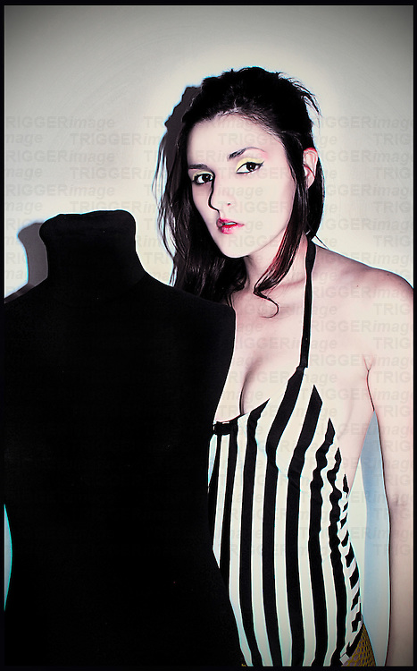 A young woman with dark hair wearing a striped swim suit standing behind a black manequin