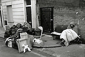 A squatter evicted from a property in Camden Town sits on the pavement with all his possessions, London 1980.
