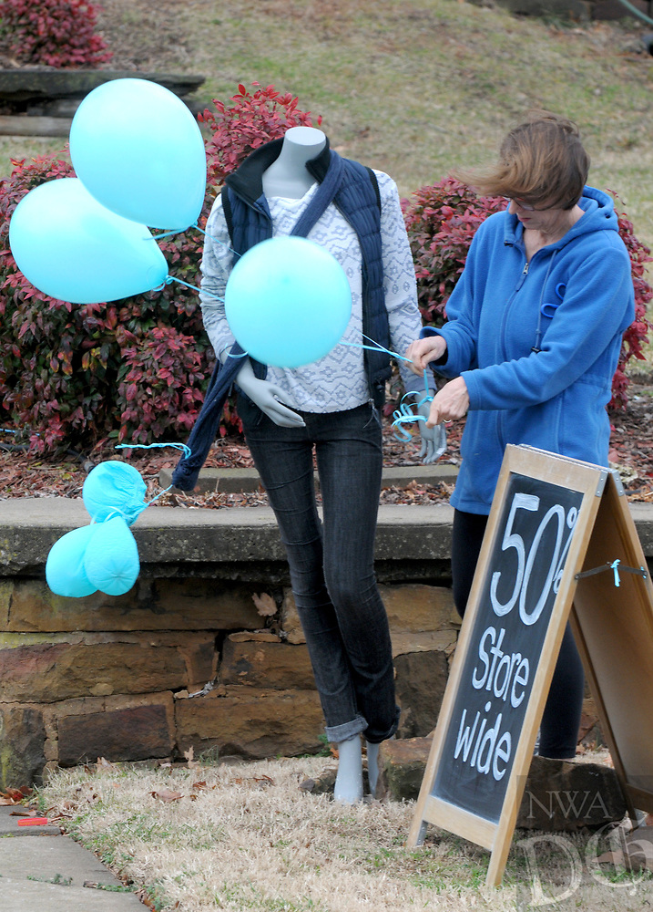 NWA Democrat-Gazette/DAVID GOTTSCHALK  Melody Taylor, executive director of Beautiful Lives Thrift Boutique, works with the wind Monday, January 7, 2019, to fasten balloons on a display mannequin at the boutique in Fayetteville. The non profit, that supports five organizations for women and children in crisis, will move at the end of the month to a new location at 245 East Township.