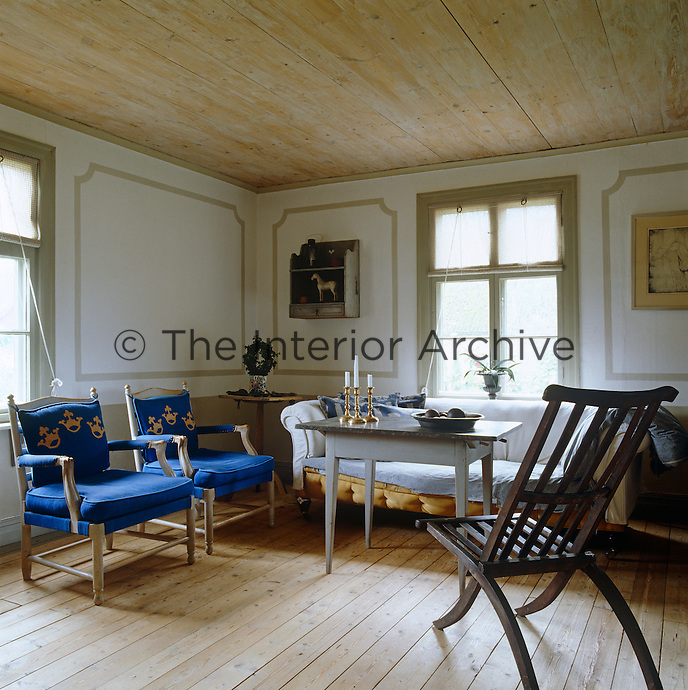 In a simple country living room a note of vivid colour comes from the ultramarine-blue upholstery of two antique chairs