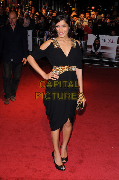 "FREIDA PINTO .Attending the 54th BFI London Film Festival screening of ""Miral"" at the Vue West End, Leicester Square, London, England, UK, October 18th 2010..full length hand on hip  black dress gold beaded cut out shoulders smiling embellished shoes peep toe clutch bag .CAP/CJ.©Chris Joseph/Capital Pictures."