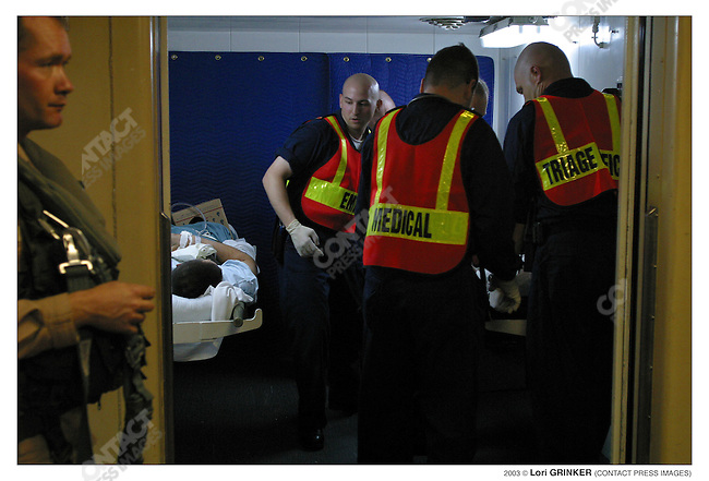 HN E3  (Hospital Corpsman),  and paramedic, Matthew Moritz (25 years old)  and the triage team, bring patients from the medical receiving area as they as they are taken off the helicopter.  USNS COMFORT Naval hospital ship in the Persian Gulf.