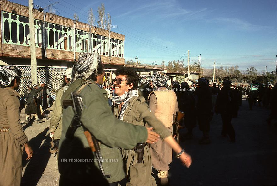 Iran 1979.Peshmergas of KDPI entering Echnou, two friends meetingt