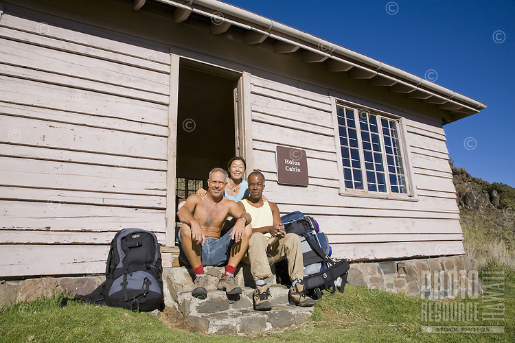 Asian-American woman, African-American man and Caucasian man sitting outside Holua Cabin in the Haleakala Crater with their backpacks