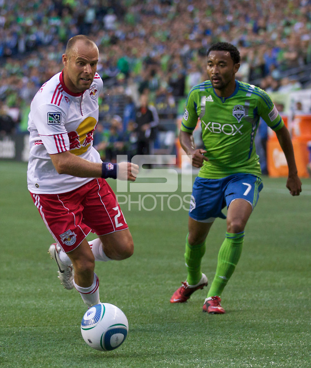 New York Red Bulls forward Joel Lindpere dribbles the ball in front of Seattle Sounders FC defender James Riley during play at Qwest Field in Seattle Saturday June 23, 2011. The Sounders won the game 4-2.