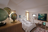 An attic bedroom is decorated with a collection of globes and the bed has a white Moroccan leather headboard
