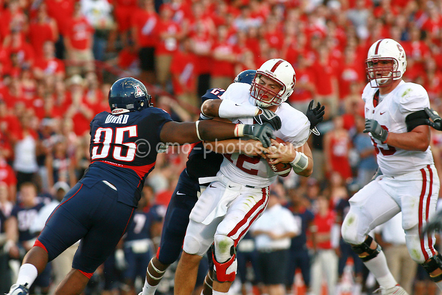 Oct 17, 2009; Tucson, AZ, USA; Stanford quarterback Andrew Luck (12) is sacked by Arizona defensive tackle Jowyn Ward (95) and safety Corey Hall (21) during the 2nd quarter of a game at Arizona Stadium.