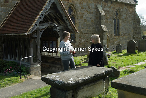 Hartfield East Sussex. St Mary the Virgin Church Hartfield. Nicholas Smith Bequest. 2014. The Rev'd Julie Sear and Mary ? who administers the Nicholas Smith Bequest wait at the tomb of  Nicolas Smith. No one came forward to claim the annual dole thats given out on Good Friday.