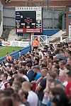 Supporters of Middlesbrough watching the closing moments at the Victoria Ground, Hartlepool, during a pre-season friendly between their team and Hartlepool United. Hartlepool were relegated to League Two at the end of the 2012-13 season whilst their Teesside neighbours remained two divisions above them in the Championship. The game ended in a no-score draw, the home team's goalkeeper Scott Flinders saving a second-half penalty from Boro's Lucas Jutkiewicz, watched by a crowd of 2307.