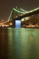"Brooklyn Bridge Illuminated at Night, New York City, New York State, USA....Waterfall installed under the bridge as part of ""The New York City Waterfalls"" project by Danish-Icelandic artist Olafur Eliasson.  This waterfall, along with three others, nearby in New York City's East River, ran from June 26 to October 13 2008, as part of an artistic project by Olafur Eliasson, presented by the Public Art Fund in collaboration with The City of New York."